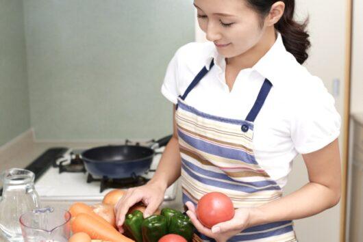 キッチンで野菜を手に取る女性