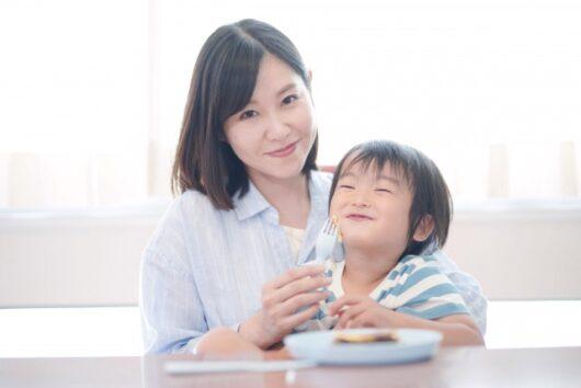 おやつを食べる男の子とママ