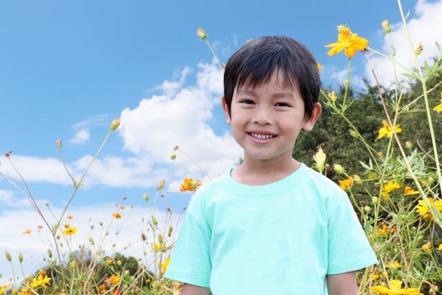 青空の下で微笑む男の子